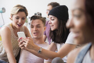 Smiling friends texting on cell phone - BLEF03431