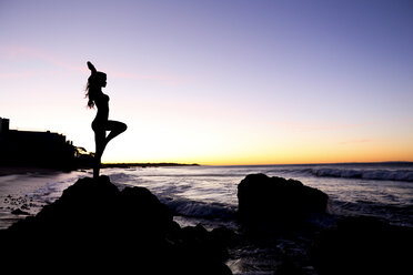 Silhouette of Caucasian woman balancing on rock at beach - BLEF03473