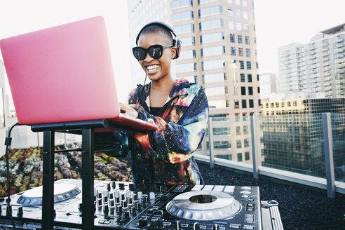 Smiling Black DJ on urban rooftop - BLEF03506