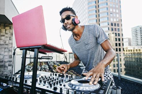 Smiling Black DJ on urban rooftop - BLEF03509
