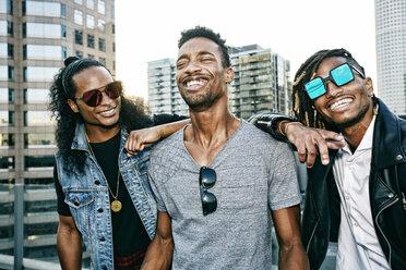 Portrait of men smiling on urban rooftop - BLEF03512