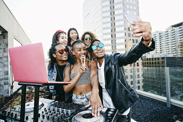 Friends posing for cell phone selfie with DJ on urban rooftop - BLEF03515