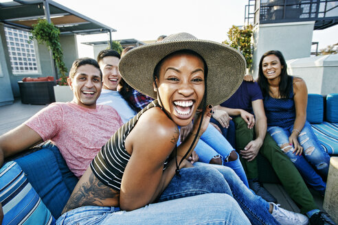 Friends laughing on rooftop sofa - BLEF03599