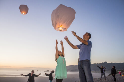 Caucasian father and daughter flying lantern balloon at beach - BLEF03641