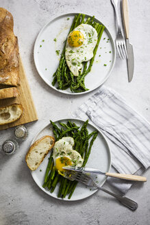 Asparagus, fried eggs and baguette on plates - GIOF06338