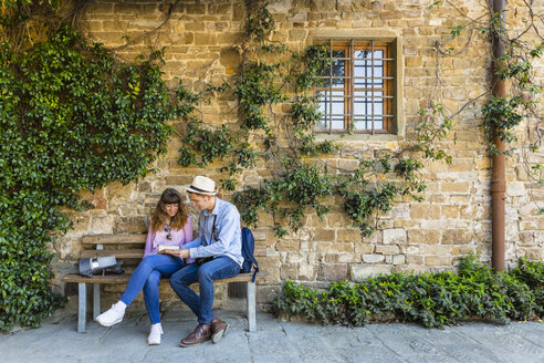 Young couple on a city break, sitting on a bench, taking a break - MGIF00417
