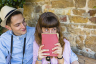 Young couple on a city break, sitting on a bench, reading guidebook - MGIF00420
