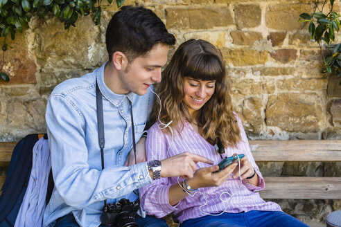 Young couple on a city break, sitting on a bench, using smartphone - MGIF00423