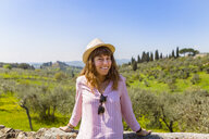 Youngwoman standing at wall in Florence, Tuscany, Italy - MGIF00435