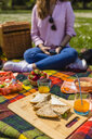 Young woman having a picnic with healthy food in a park - MGIF00453