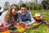 Young couple having a picnic with healthy food in a park - MGIF00459