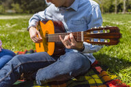 Young man playing the guitar in a park - MGIF00462