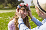 Young man putting flowers on on his girlfriend's head - MGIF00465