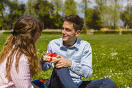 Young woman gifting her boyfriend with a present in a park - MGIF00468