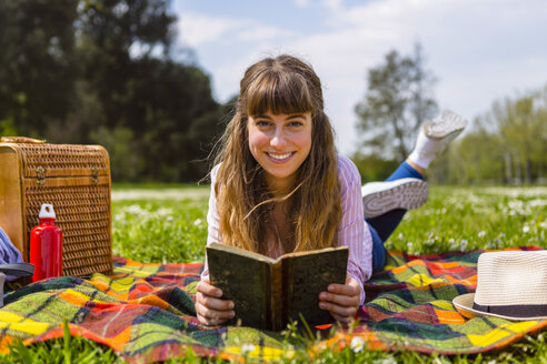 Young woman lying on a picnic blanket, reading a book in a park - MGIF00471