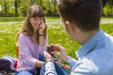Young man proposing to his girlfriend in a park - MGIF00474
