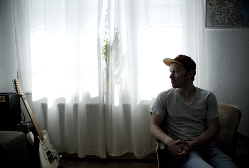 Man sitting in front of window, looking at his guitar - FLLF00144