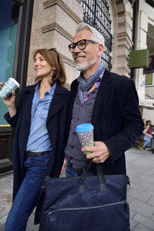 Smiling mature couple with reusable bamboo cups walking in the city - ECPF00739