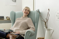 Happy woman sitting in armchair at home with tablet - FLLF00155