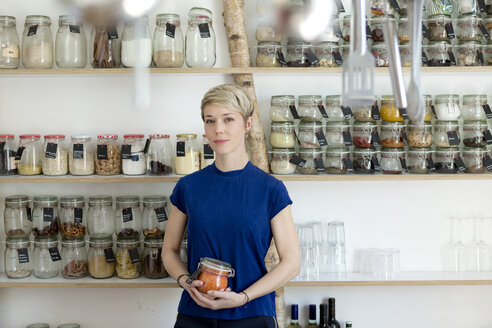 Portrait of woman holding jar in front of spice shelf in kitchen - FLLF00167