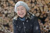 Portrait of happy woman in snowfall - PSIF00262