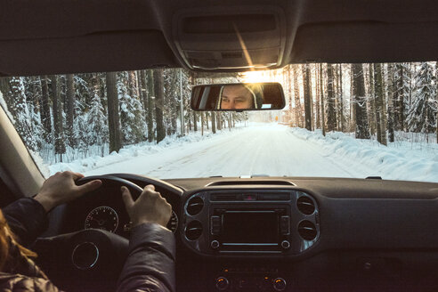 Finland, Kuopio, woman driving car in winter landscape at sunset - PSIF00268