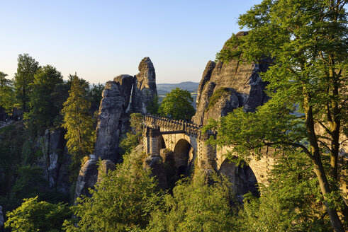 Germany, Saxony, Elbe Sandstone Mountains, view to the Bastei rock formation at sunrise with Bastei Bridge - RUEF02196