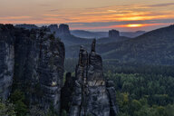 Germany, Saxony, Elbe Sandstone Mountains, sandstone rock Brosinnadel with Falkenstein and Schrammsteine in background at sunset - RUEF02226