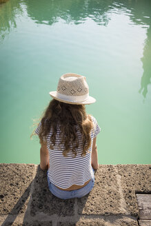 Italy, Tuscany, Back view of a girl sitting at swimming pool - OJF00342