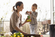 Mother and daughter planting flowers together on balcony - DIGF07033