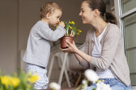 Cute little girl smelling at flower held by her mother - DIGF07042