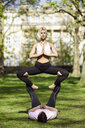 Young couple doing yoga acrobatics in an urban park - JSMF01077