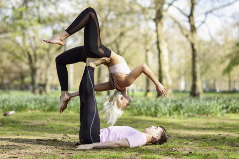 Young couple doing yoga acrobatics in an urban park - JSMF01080
