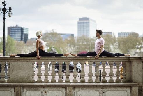 UK, London, young couple doing gymnastic acrobatics on parapet at Buckingham Palace - JSMF01089