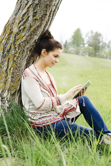 pretty, young woman with black hair sitting in a green meadow, leaning against a tree and working with her tablet, lower austria, austria - HMEF00368