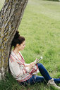 Young woman sitting at a tree in the countryside using tablet - HMEF00371