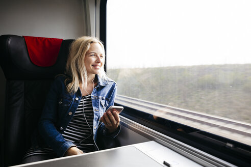 Happy blond woman listening music with smartphone and earphones travelling by train - HMEF00376