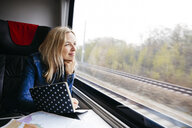 Portrait of smiling blond woman with notebook travelling by train looking out of window - HMEF00379