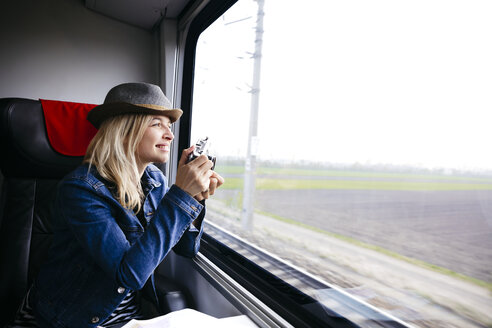 young, pretty, blonde woman travels by train and sits directly at the window - HMEF00382