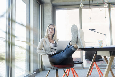 Relaxed businesswoman using laptop in office with feet up - UUF17462