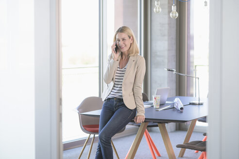 Businesswoman talking on cell phone in office - UUF17477