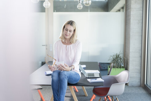 Businesswoman sitting on desk in office using cell phone - UUF17486