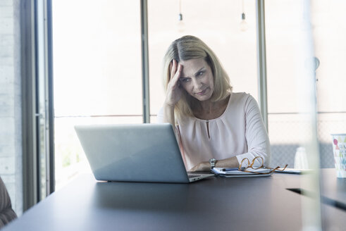 Stressed businesswoman using laptop in office - UUF17495