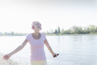 Happy mature woman listening to music with headphones at the riverside - UUF17564