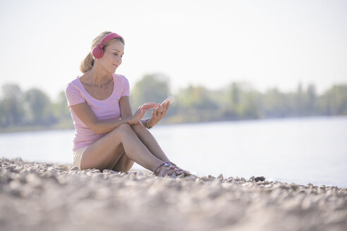 Mature woman relaxing at the riverside listening to music with headphones and using cell phone - UUF17570