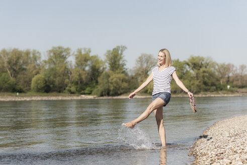 Carefree mature woman splashing in a river - UUF17591