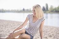 Smiling mature woman sitting at the riverside - UUF17594
