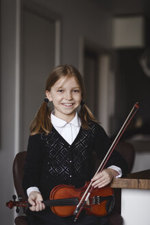 Portrait of a smiling girl with a violin at home - EYAF00243
