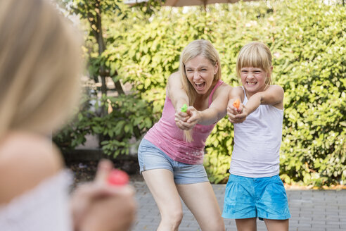Mother and two girls splashing with water guns in garden - SHKF00807