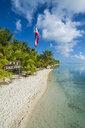 French Polynesia, Tuamotus, Tikehau, palm beach with flag - RUNF02074